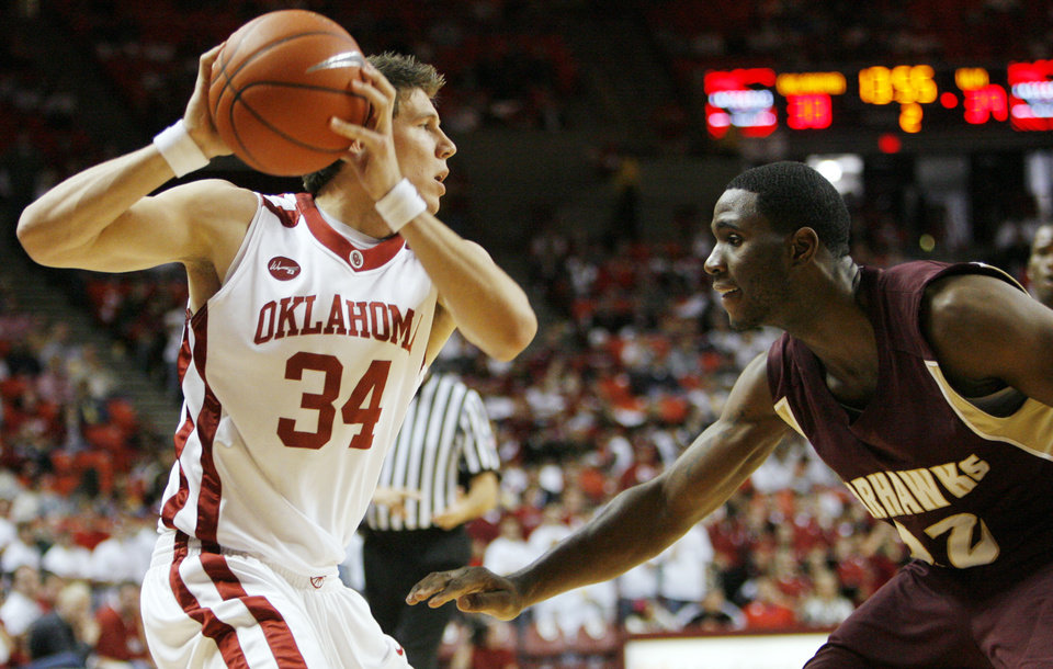 Photo - OU's Cade Davis (34) looks to pass around Lawrence Gilbert (22) of ULM during the second half of the men's college basketball game between the Oklahoma Sooners and Louisiana-Monroe at Lloyd Noble Center in Norman, Okla., Tuesday, Nov. 17, 2009. OU won, 72-61. Photo by Nate Billings, The Oklahoman