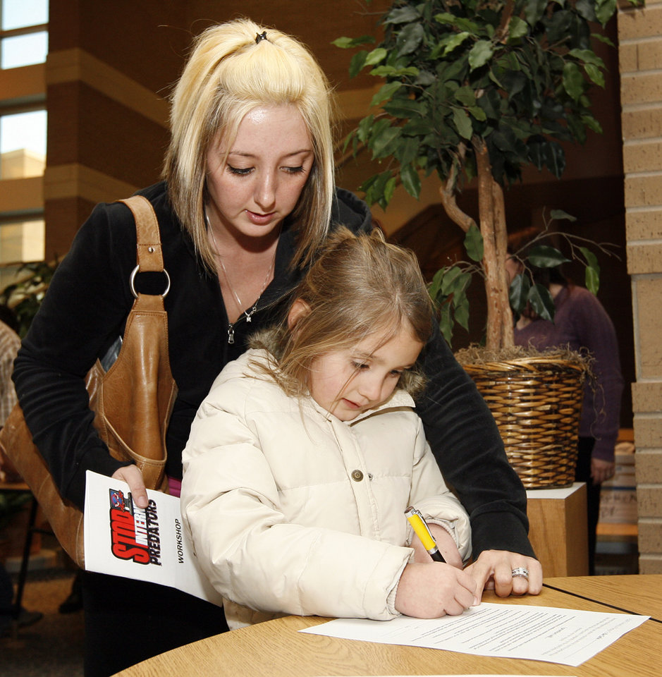Kenna Mason helps her daughter Briley Mason, 7, sign a pledge to use the internet safely before the Stop Internet Predators workshop at the Nancy O'Brien Center for the Performing Arts on the Norman North High School campus in Norman, Okla., February 26, 2008. BY NATE BILLINGS, THE OKLAHOMAN
