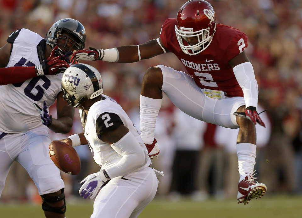 Photo - Oklahoma's Julian Wilson (2) leaps towards TCU's Trevone Boykin (2) during a college football game between the University of Oklahoma Sooners (OU) and the TCU Horned Frogs at Gaylord Family-Oklahoma Memorial Stadium in Norman, Okla., on Saturday, Oct. 5, 2013. Photo by Bryan Terry, The Oklahoman