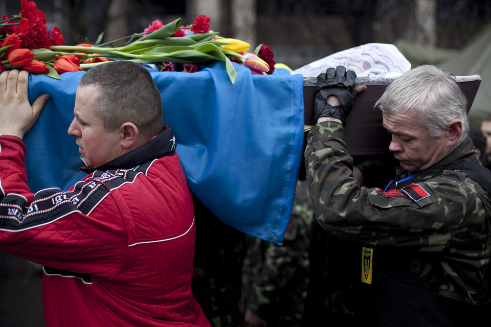 Photo - Pallbearers carry a coffin bearing the body of Andryi Pozniak, 25, a self defense volunteer who was shot and killed by an unknown assailant two days ago near Kiev's Independence Square, Ukraine, Thursday, March 6, 2014. (AP Photo/David Azia)
