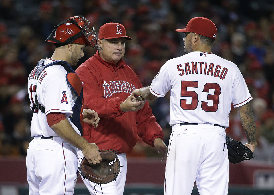 Photo - Los Angeles Angels starting pitcher Hector Santiago, right, is relieved by manager Mike Scioscia, center, during the sixth inning of a baseball game against the Seattle Mariners on Wednesday, April 2, 2014, in Anaheim, Calif. At left is catcher Chris Iannetta. (AP Photo/Jae C. Hong)