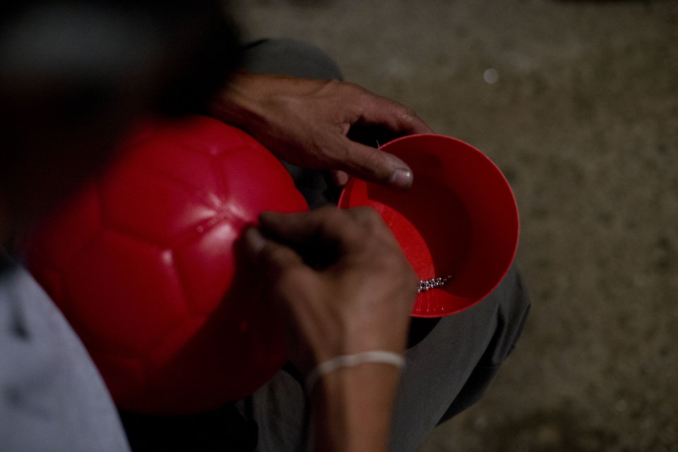 """Photo - In this Friday, June 6, 2014 photo, Italia goalkeeper and industrial mechanic Miguel Angel Canela inserts metal pellets into a plastic ball to give it the right sound and weight for the blind players to follow, at his home workshop in the Valle de Chalco area of Estado de Mexico. When the league first started, says Canela, """"they used a soda can filled with pebbles, so they heard it make noise. From there, they went to the market and bought some soccer balls, and we put ball bearings inside. That's the same ball we play with today."""" The only difference now is that Canela makes the plastic balls himself using a mold. (AP Photo/Rebecca Blackwell)"""