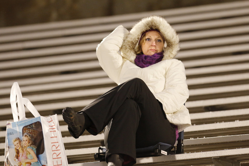 Motherly love shown by Vonda McCoy as she waits in the wind and cold to watch her daughter, who is an Edmond North cheerleader, during the high school football game between Norman North and Edmond North in Edmond at Wantland Stadium Friday, Friday, October 18, 2013.  Photo by Doug Hoke, The Oklahoman