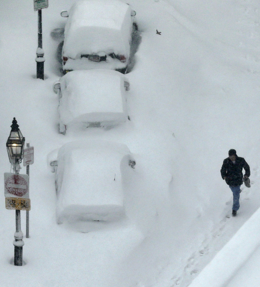 Photo - A man walks past snow covered cars in the South End neighborhood of Boston, Saturday, Feb. 9, 2013. The Boston area received about two feet of snow from a winter storm. (AP Photo/Charles Krupa)