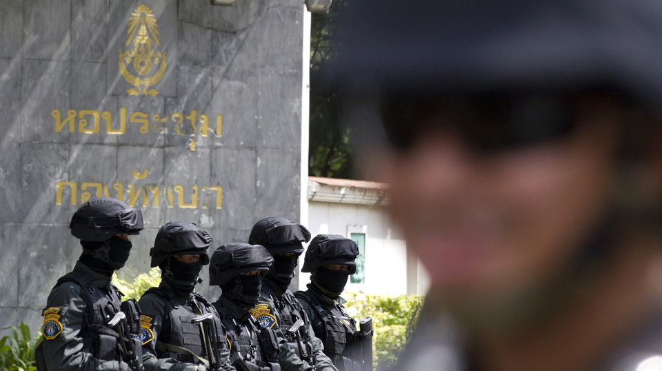 Photo - Thai police commando stand guard outside the Army Club before Thai former Prime Minister Yingluck Shinawatra  arrive to report to Thailand's ruling military in Bangkok, Thailand, Friday, May 23, 2014. The military on Friday summoned the entire ousted government and members of the politically influential family at the heart of the country's long-running conflict, a day after it seized control of this volatile Southeast Asian nation in a non-violent coup. It was unclear why more than 100 people,  including the ousted prime minister and several members of the influential Shinawatra family, were ordered to report to the military, which said it was summoning the high-profile figures
