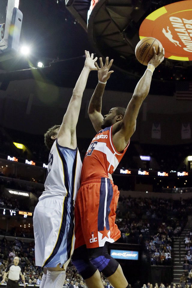 Photo - Washington Wizards forward Trevor Booker, right, shoots over Memphis Grizzlies center Marc Gasol, of Spain, during the first half of an NBA basketball game in Memphis, Tenn., Friday, Feb. 1, 2013. (AP Photo/Danny Johnston)