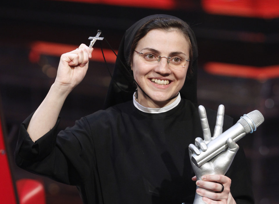 Photo - Sister Cristina Scuccia poses with the trophy and holding the cross on the stage after winning the final of the Italian version of the TV talent show