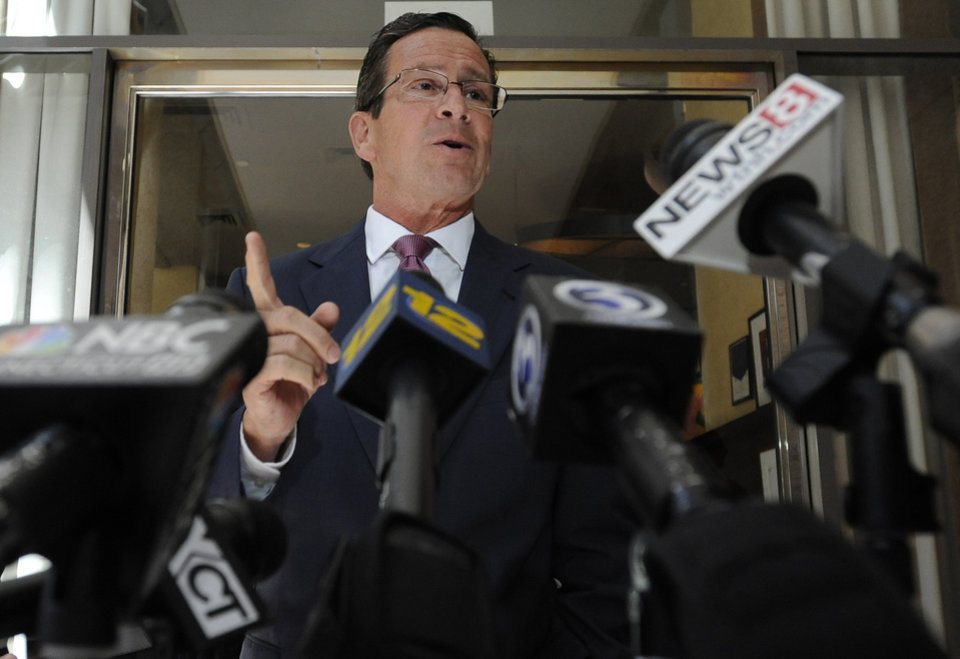 Photo - Connecticut Gov. Dannel P. Malloy briefly speaks to the media after stopping by a restaurant to welcomeTexas Gov. Rick Perry in Hartford, Conn., Monday, June 17, 2013. Perry was at the restaurant hosting a lunch appointment with Connecticut gun makers. The governors of Texas and South Dakota are visiting Connecticut to court local gun makers, many of which have threatened to leave since the state passed tough new gun-control laws in response to the massacre at Sandy Hook Elementary School. . (AP Photo/Jessica Hill)