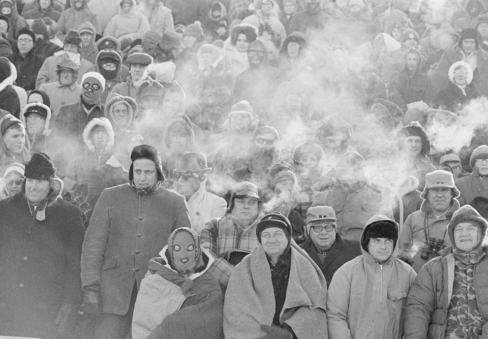 Photo - FILE - In this Dec. 31, 1967 file photo, fans watch the Green Bay Packers play the Dallas Cowboys in the NFL Championship game in Green Bay, Wisc. Comparisons to the legendary 1967 Ice Bowl are inevitable when the mercury dips below zero at Lambeau Field. But even if temperatures sink to minus 13 Sunday, Jan. 5, 2014, at the 49ers-Packers playoff game, modern technology will ensure fans are warmer than their predecessors.  (AP Photo/File)