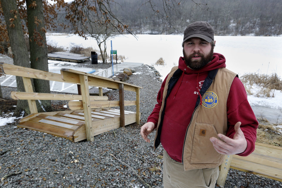 Photo - In this Friday, Jan. 10, 2014 photo, Kevin Garrison, the superintendent of parks for Washington County, tells how money from gas well royalties paid for the development and construction of the new Lynn Portal Access Area behind him for Cross Creek Lake at their Cross Country County Park in Avella, Pa. Local officials say the deals have worked well, and that they have few other options to generate new funds. But some residents don't like drilling taking place under public land. (AP Photo/Keith Srakocic)