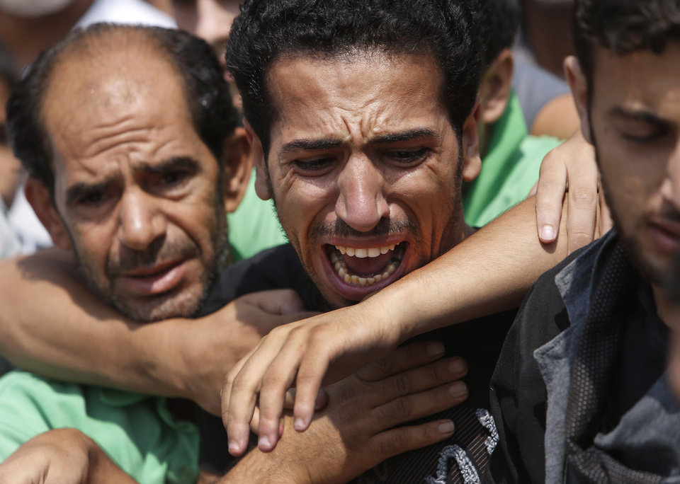 Photo - A relative bursts into tears as mourners try to comfort him as they gather around the bodies of seven members of the Kelani family, killed overnight by an Israeli strike in Gaza City, during their funeral in Beit Lahiya, northern Gaza Strip, on Tuesday, July 22, 2014. Ibrahim Kelani, 53, his wife Taghreed and their five children, were killed in the strike on a Gaza City high rise. Ibrahim's brother Saleh Kelani said Tuesday that his brother and his brother's children, ranging in age from four to 12, had German citizenship, while his wife had not. The family had rented the apartment in the high-rise after fleeing their home in the northern Gaza town of Beit Lahiya which came under heavy shelling by the Israeli army. (AP Photo/Lefteris Pitarakis)