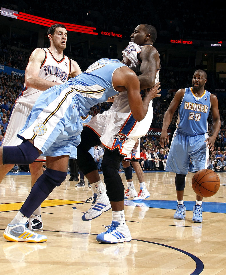 Photo - Denver's Nene (31) pushes Oklahoma City's Kendrick Perkins (5) during the NBA basketball game between the Oklahoma City Thunder and the Denver Nuggets, Friday, April 8, 2011, at the Oklahoma City Arena.. Photo by Sarah Phipps, The Oklahoman