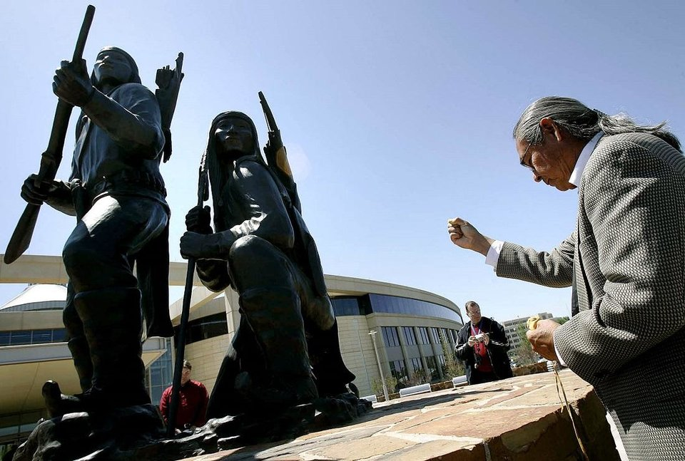 Photo - Phillip Houser uses ceremonial pollen, or medicine, to bless artwork created by his father Allan Houser during the unveiling and dedication of the bronze statue, titled