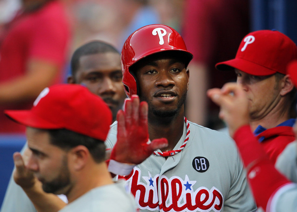 Photo - Philadelphia Phillies left fielder Domonic Brown (9) celebrates with teammates after scoring on a wild pitch in the fourth inning of a baseball game Tuesday, June 17, 2014, in Atlanta. (AP Photo/Todd Kirkland)