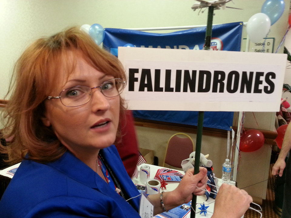 Photo - Kaye Beach, a delegate  from Norman to the Oklahoma Republican State Convention, poses with her sign that criticizes Gov. Mary Fallin's opposition this year to legislation that would have placed restrictions on drones.  BY MICHAEL MCNUTT - THE OKLAHOMAN