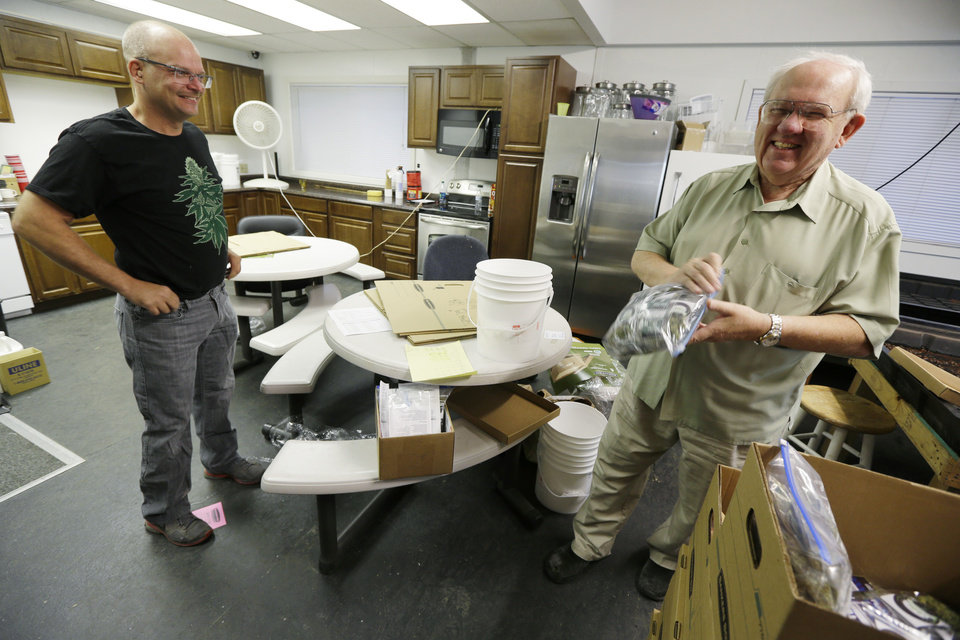 Photo - Bob Leeds, owner of Sea of Green Farms, right, has a laugh with farm director Phil Tobias, as they load packets of recreational marijuana into boxes, Tuesday, July 8, 2014, in Seattle, for delivery to a store in Bellingham, Wash. It was the first delivery for the company since retail licenses were issued by the state on Monday. (AP Photo/Ted S. Warren)