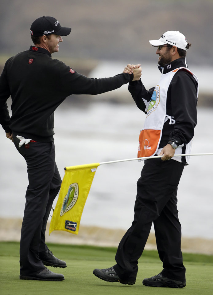 Photo - Jimmy Walker, left, celebrates with his caddie Andy Sanders on the 18th green on Sunday, Feb. 9, 2014, after winning the AT&T Pebble Beach Pro-Am golf tournament in Pebble Beach, Calif. (AP Photo/Eric Risberg)