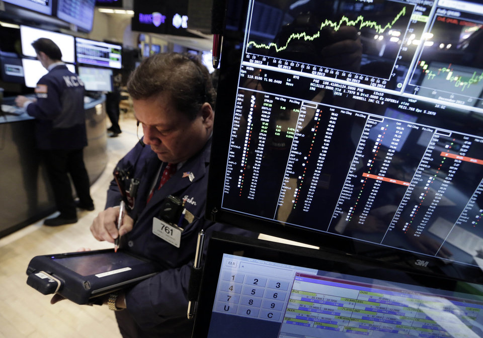 Photo - Trader John Santiago works on the floor of the New York Stock Exchange Monday, Jan. 27, 2014. Shaky economies and currencies in emerging markets are prompting more declines in global markets, following a rout last week  (AP Photo/Richard Drew)