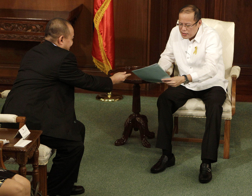 Photo -   Philippine President Benigno Aquino III, right, receives documents from Philippine government negotiator Marvic Leonen during their meeting at the Malacanang presidential palace in Manila, Philippines on Monday, Oct. 8, 2012. The Philippine government and the country's largest Muslim rebel group reached a preliminary peace deal that is a major breakthrough toward ending a decades-long insurgency that killed tens of thousands and held back development in the south. (AP Photo/Aaron Favila)