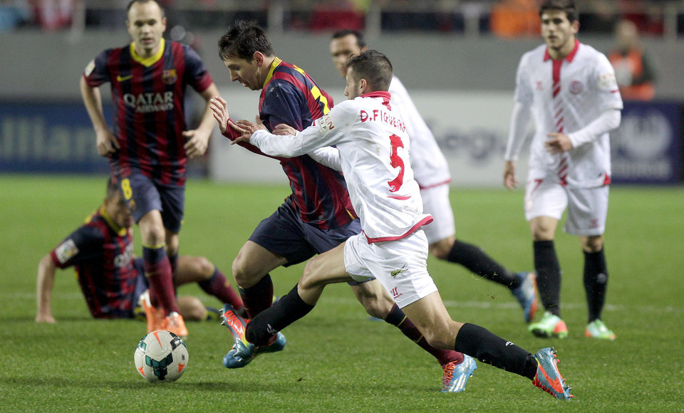 Photo - Barcelona's Lionel Messi, second left, and Sevilla's Diogo Figueiras, second right, fight for the ball during their La Liga soccer match at the Sanchez Pizjuan stadium, in Seville, Spain on Sunday, Feb. 9, 2014. (AP Photo/Miguel Angel Morenatti)