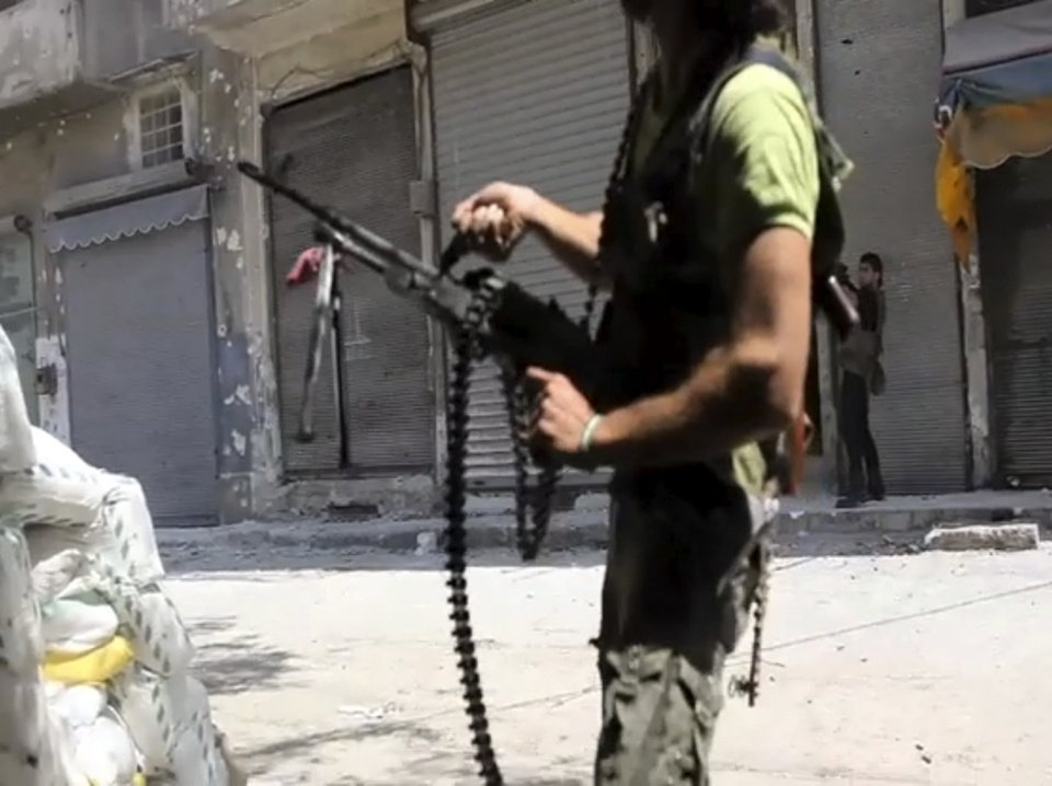 Photo -   In this image made from video and accessed Saturday, Sept. 1, 2012, Free Syrian Army fighters take up positions during fighting with Syrian troops in Aleppo, Syria. Syrian troops bombarded the northern city of Aleppo Saturday with warplanes and mortar shells as soldiers clashed with rebels in different parts of Syria's largest city, activists said. The Britain-based Syrian Observatory for Human Rights said the clashes were concentrated in several tense neighborhoods where some buildings were damaged and a number of people were wounded. (AP Photo via AP video)