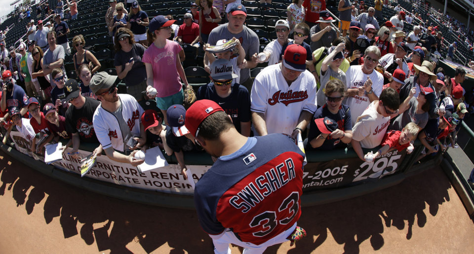 Photo - In this photo shot with a fisheye lens, Cleveland Indians' Nick Swisher signs autographs for fans before a spring exhibition baseball game against the Texas Rangers on Tuesday, March 25, 2014, in Goodyear, Ariz. (AP Photo/Darron Cummings)