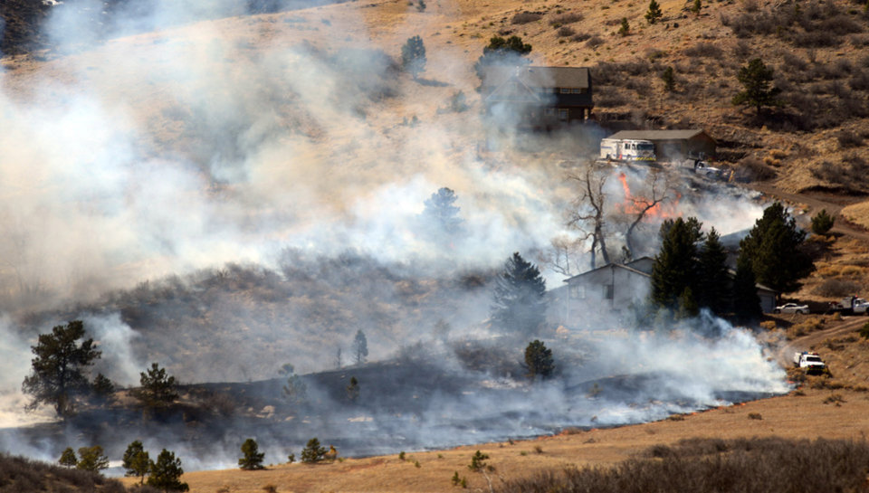 Photo - Firefighters attack to keep a line during the fire that started near Lory State Park in Fort Collins, Colo. Friday March 15, 2013. The 40-acre wildfire burning in gusty winds and warm weather was threatening homes west of Fort Collins on Friday and prompted about 50 people to leave the area. (AP Photo/The Coloradoan, V. Richard Haro)