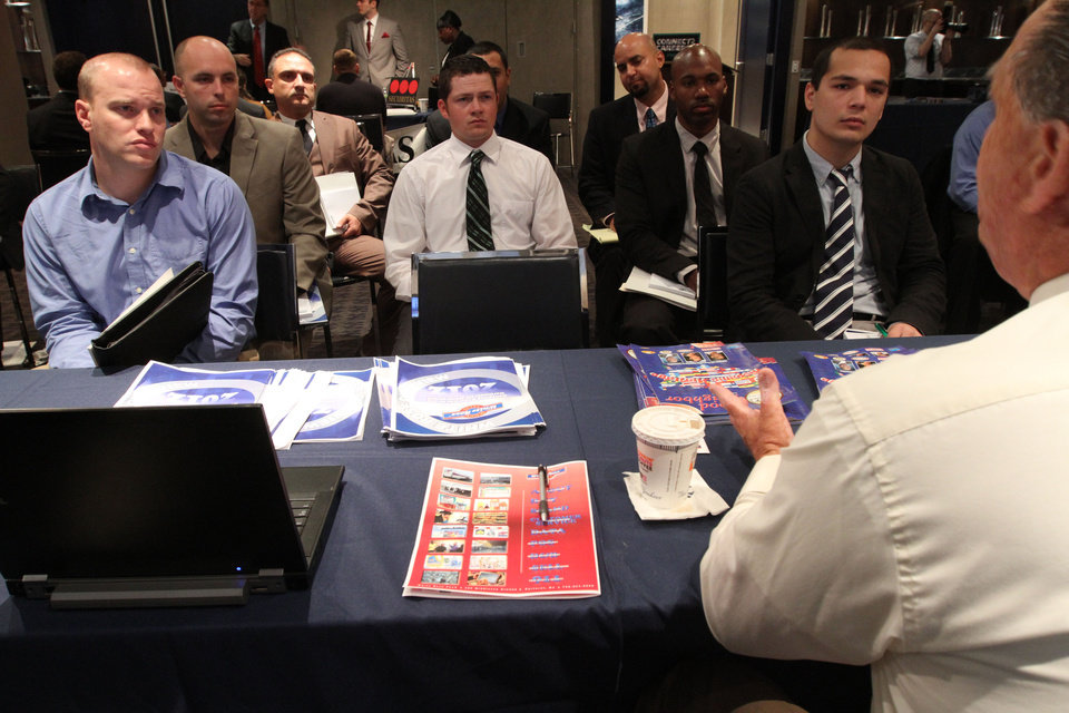 Photo -   In this Friday Sept. 28, 2012, photo, a group of veterans listen as a representative from White Rose Foods, foreground right, talks about their agency during a job fair introducing veterans to careers in the security and private investigations industry at Yankee Stadium in the Bronx borough of New York. Weekly applications for U.S. unemployment benefits jumped 46,000 in the week ending on Thursday, Oct.18, 2012, to a seasonally adjusted 388,000, the highest in four months. The increase represents a rebound from the previous week's sharp drop. Both swings were largely due to technical factors. (AP Photo/Tina Fineberg)