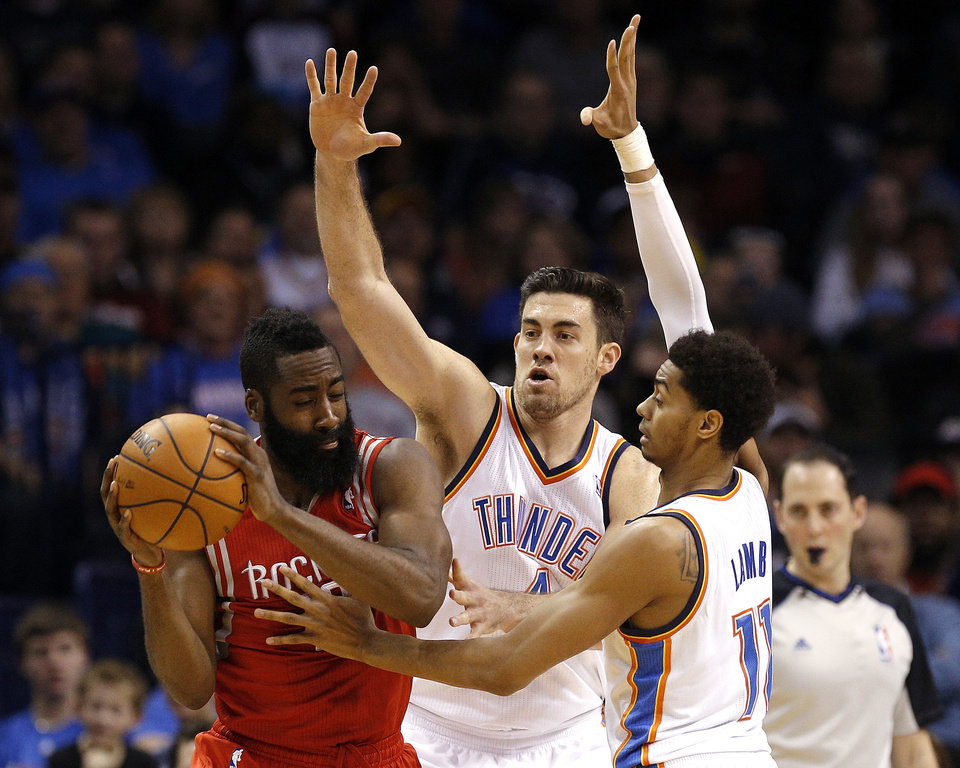 Photo - Oklahoma City 's Nick Collison (4) and Jeremy Lamb (11) defends against Houston's James Harden (13) during the NBA game between the Oklahoma City Thunder and the Houston Rockets at the Chesapeake Energy Arena  in Oklahoma City, Sunday, Dec. 29, 2013. Photo by Sarah Phipps, The Oklahoman