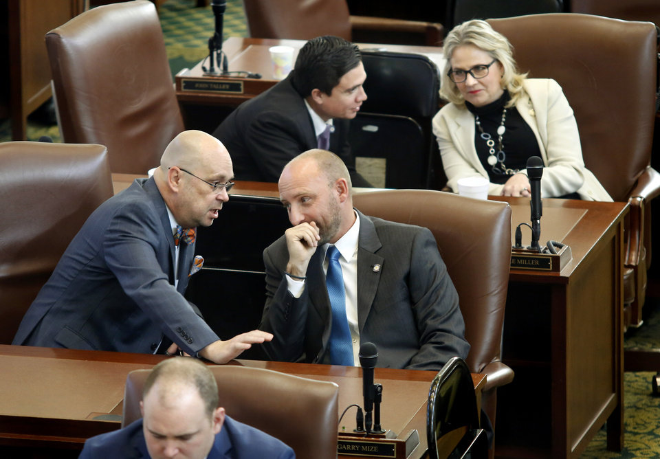 Photo - Foreground, Mike Osburn, left, talks to deskmate Garry Mize while Ryan Martinez leans in to speak with Nicole Miller at their seats on the floor of the House. The state Legislature met in their separate chambers at the state Capitol Tuesday afternoon, Jan. 8, 2019, for an organizational day.  Senators joined state representatives in the House to conduct a brief joint session. Photo by Jim Beckel, The Oklahoman.