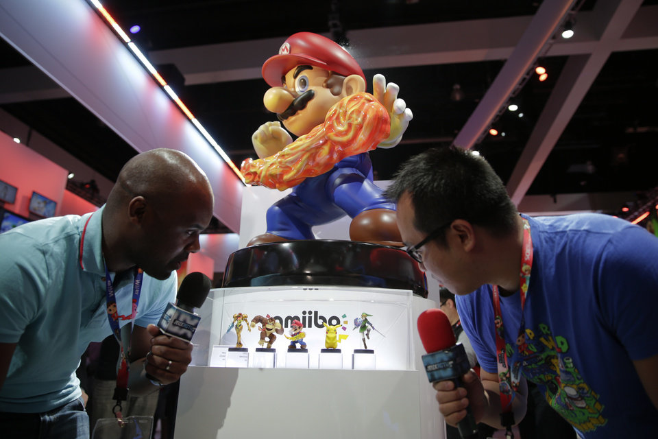 Photo - French television reporters look at Amiibo characters for Wii U at the Nintendo booth during the Electronic Entertainment Expo on Tuesday, June 10, 2014, in Los Angeles. (AP Photo/Jae C. Hong)