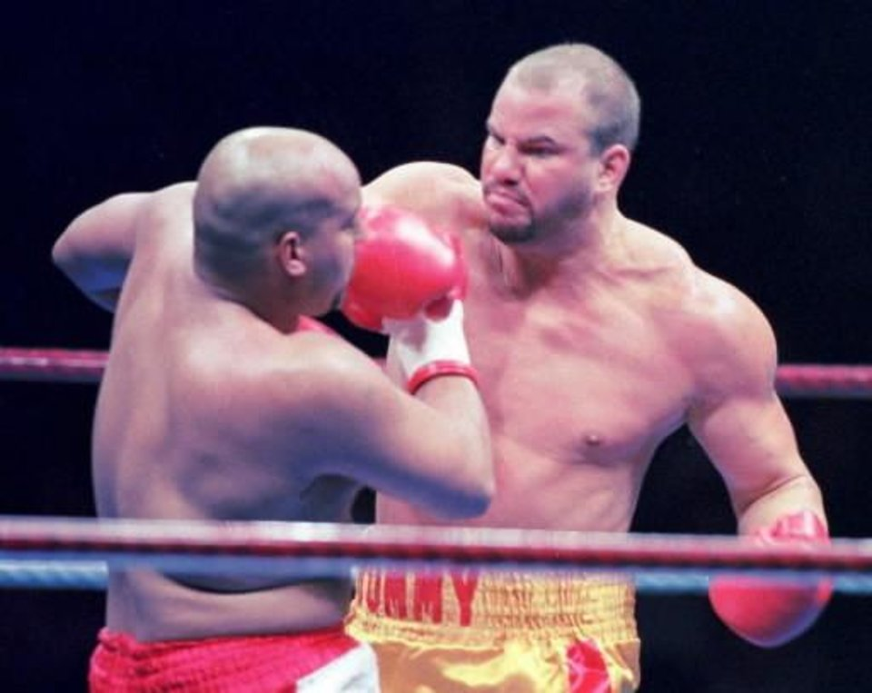Photo - Former heavyweight champion Tommy Morrison, right, gives a right against Marcus Rhode in the first round in their undercard bout in Urayasu, east of Tokyo, in this Nov. 3, 1996 file photo. Morrison, whose boxing career came to a sudden halt when he tested positive for the AIDS virus, is now serving a two-year prison sentence for drug and weapon charges at the Southwest Arkansas Community Punishment Center in Texarkana, Ark. (AP Photo/Katsumi Kasahara, File)