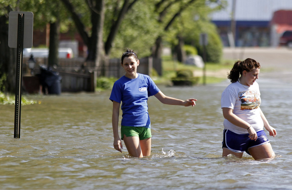 Photo - Girls wade through floodwaters down a street on Wednesday, April 27, 2011, in West Memphis, Ark. Strong storms hit the South Wednesday for the second straight day. (AP Photo/Mark Humphrey)