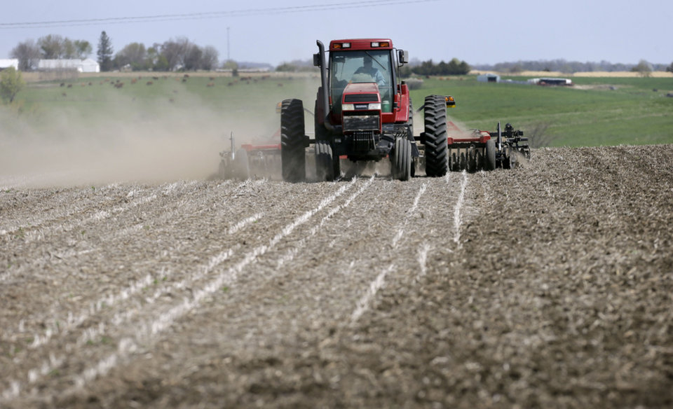 A farmer works in a field, Monday, May 5, 2014, near De Soto, Iowa. Despite getting a late start to planting, farmers are optimistic they'll get their crops planted during the optimum period. Due to rain and cold, it will just be toward the mid to later part of that period. (AP Photo/Charlie Neibergall)