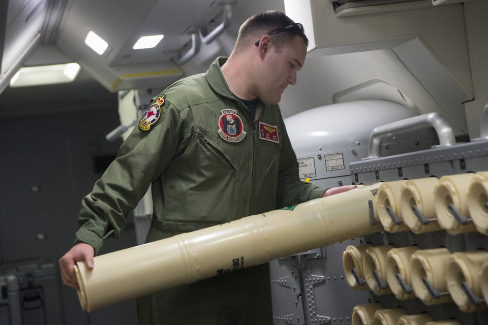 Photo - In this photo taken on Thursday, April 10, 2014, and released by the U.S. Navy, Airman 2nd Class Karl Shinn unloads a sonobuoy from a rack onboard a P-8A Poseidon aircraft, during a search mission looking for missing Malaysia Airlines flight MH370 over the southern Indian Ocean. Sonobuoys are used to detect frequencies and signals in the water.  (AP Photo/U.S. Navy, Chief Spc. Keith DeVinney)