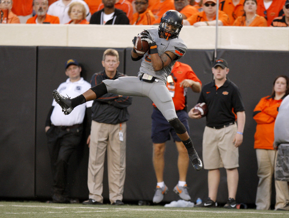 Photo - Oklahoma State's Josh Stewart (5) catches a pass during a college football game between Oklahoma State University (OSU) and West Virginia University at Boone Pickens Stadium in Stillwater, Okla., Saturday, Nov. 10, 2012. Oklahoma State won 55-34. Photo by Bryan Terry, The Oklahoman