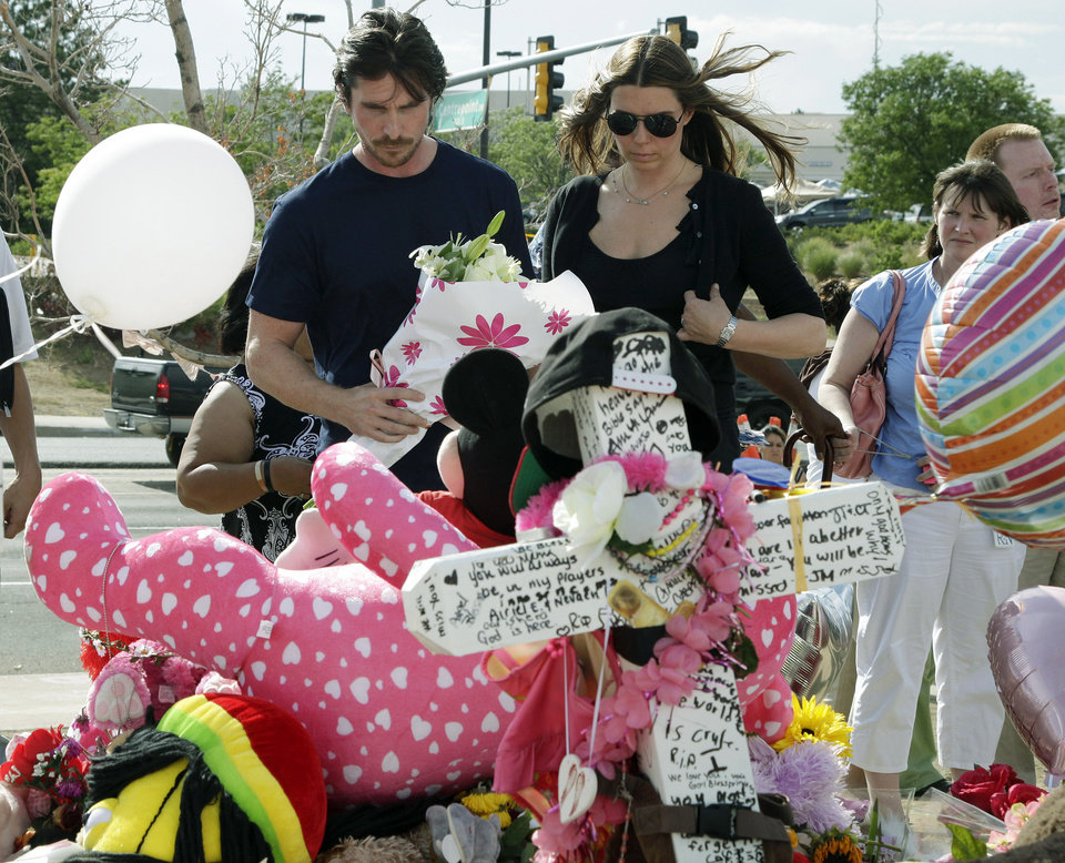 Photo -   Actor Christian Bale and his wife Sibi Blazic view a cross and large display of flowers and stuffed animals dedicated to Veronica Moser-Sullivan, 6, the youngest of the 12 victims of Friday's mass shooting, Tuesday, July 24, 2012, at a memorial in Aurora, Colo. Twelve people were killed when a gunman opened fire during a late-night showing of the movie