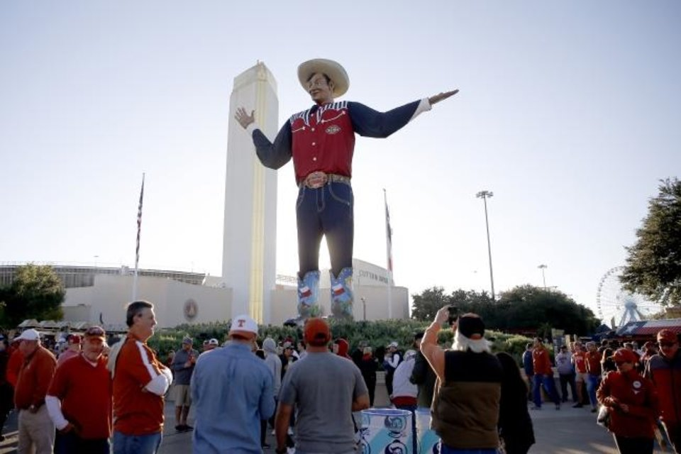 Photo -  Fans walk past Big Tex before the Red River Showdown college football game between the University of Oklahoma Sooners (OU) and the Texas Longhorns (UT) at Cotton Bowl Stadium in Dallas, Saturday, Oct. 12, 2019. [Bryan Terry/The Oklahoman]