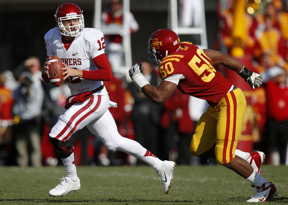 Photo - Oklahoma's Landry Jones (12) tries to get away from Iowa State's Willie Scott (50) during a college football game between the University of Oklahoma (OU) and Iowa State University (ISU) at Jack Trice Stadium in Ames, Iowa, Saturday, Nov. 3, 2012. Photo by Bryan Terry, The Oklahoman