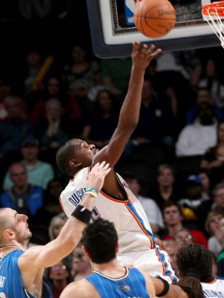 Photo - Oklahoma City's Kevin Durant puts up a shot in front of Orlando's defense during the NBA basketball game between the Orlando  Magic and the Oklahoma City  Thunder at the Ford Center in Oklahoma City, on Sunday, Nov. 8, 2009. The  Thunder beat the  Magic 102-74. By John Clanton