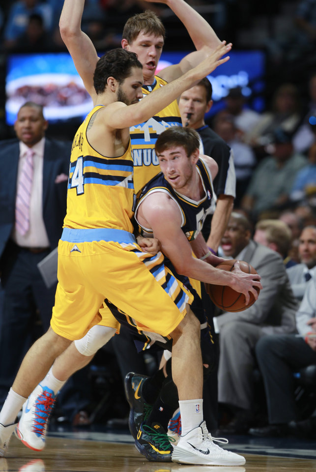 Photo - Utah Jazz forward Gordon Hayward, front right, is trapped with the ball by Denver Nuggets guard Evan Fournier, front left, of France, and center Timofey Mozgov, back, of Russia, in the first quarter of an NBA basketball game in Denver on Saturday, April 12, 2014. (AP Photo/David Zalubowski)