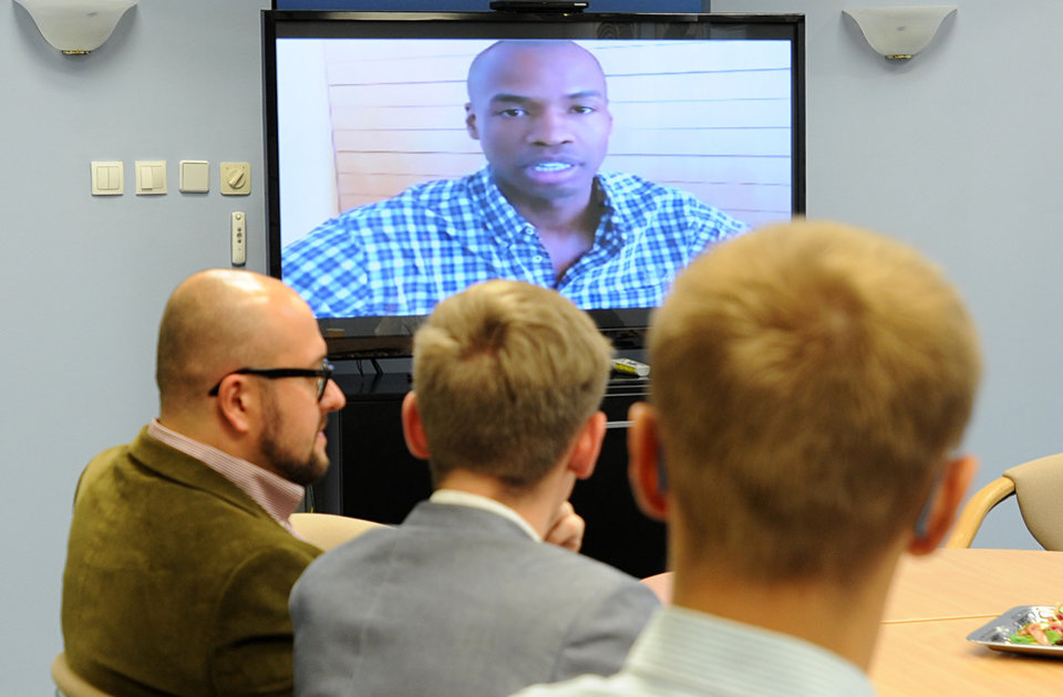 Photo - In this  picture taken June 24 2014  gay rights advocates listen as NBA player Jason Collins talks about being openly gay in a live TV link-up, at the U.S. Embassy in Warsaw, The chat with Collins was seen simultaneously by groups at U.S. embassies in Warsaw, Prague, Vienna and Ottawa. The program was one of many global efforts undertaken by the U.S. to promote the gay rights.  (AP Photo/Alik Keplicz)