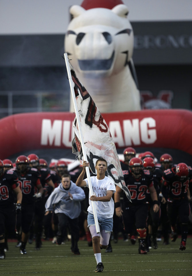 Photo - Patrick Osborne, a senior, leads the Mustang Broncos onto the field during a high school football game between Mustang and Stillwater in Mustang, Okla., Friday, Sept. 14, 2012.  Photo by Garett Fisbeck, The Oklahoman