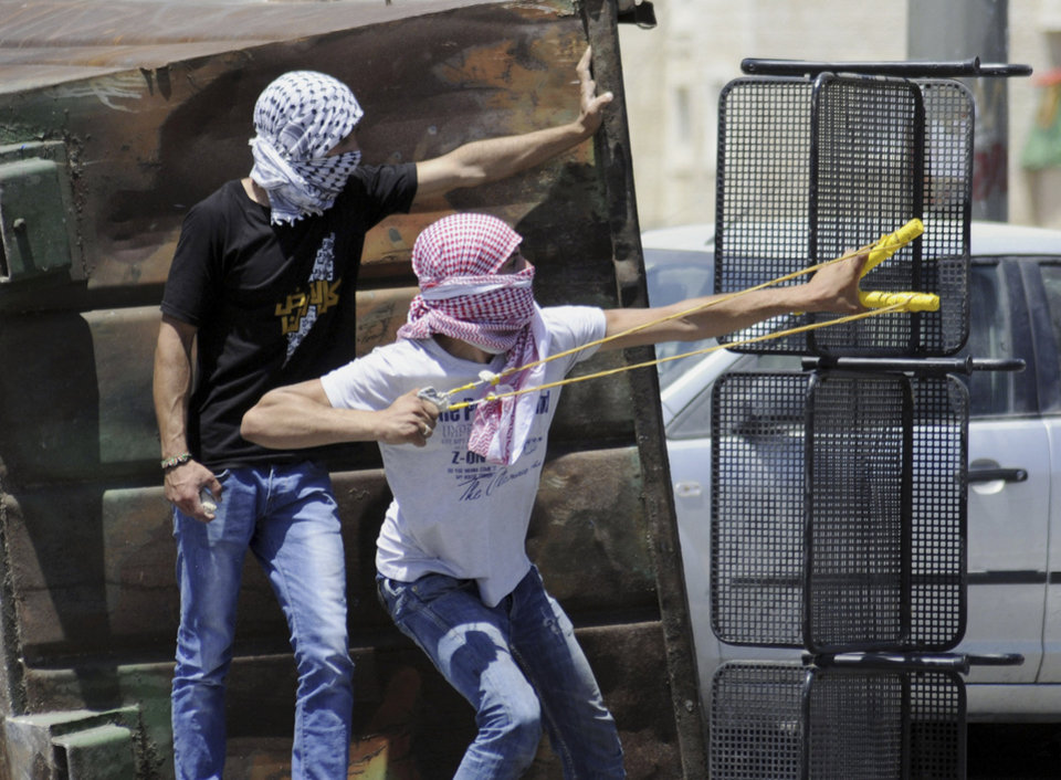 Photo - A Palestinian uses a sling shot during clashes with Israeli border police in Jerusalem on Wednesday, July 2, 2014. The suspected abduction of an Arab teen followed by the discovery of a body in Jerusalem on on Wednesday ignited clashes between Israeli police and stone-throwing Palestinians, who saw it as a revenge attack for the killing of three Israeli teens in the West Bank. (AP Photo/Mahmoud Illean)