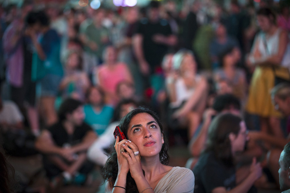 Photo -   A spectator watches a live stream of the Mars Curiosity landing while listening to an audio broadcast on her phone among the hundreds of other on-lookers in Times Square, August 6, 2012, in New York. After traveling 8 1/2 months and 352 million miles, Curiosity landed on Mars Sunday night. (AP Photo/John Minchillo)