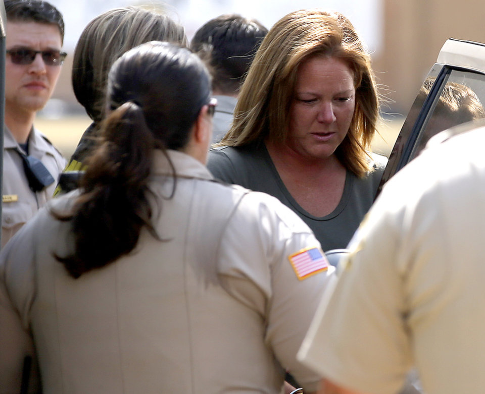 Photo - Jennifer Niles is led away from the Garfield County Courthouse in Enid, Okla., Tuesday, July 25, 2017, after being indicted in connection with the death of an inmate. Photo by Bryan Terry, The Oklahoman