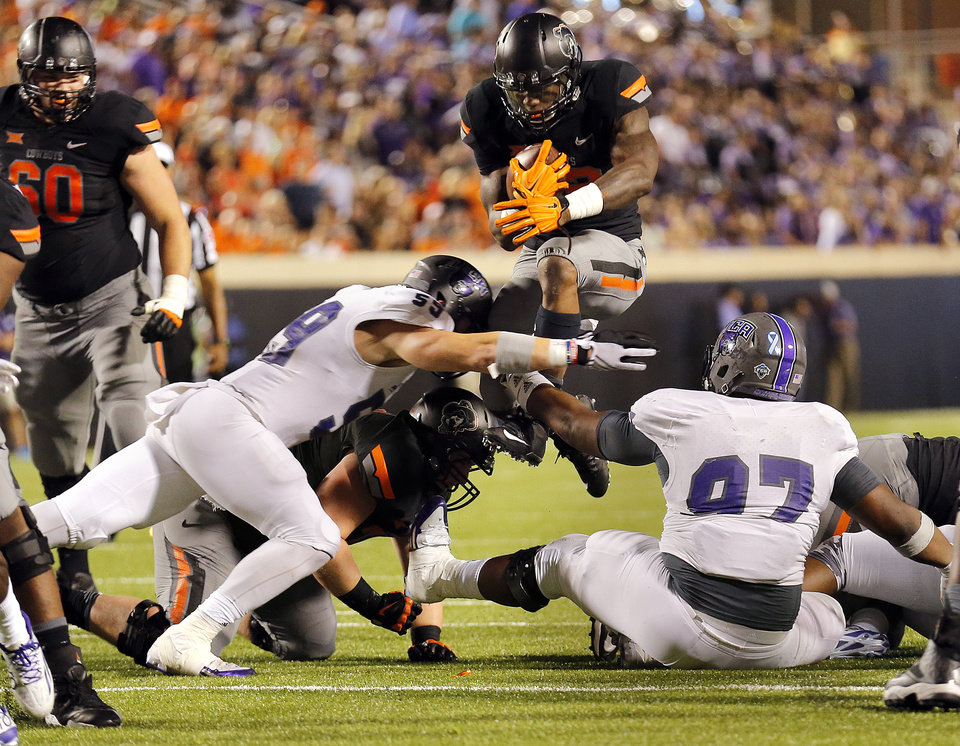 Photo - Oklahoma State's Chris Carson (32) leaps over defenders in the third quarter during the college football game between the Oklahoma State Cowboys (OSU) and the Central Arkansas Bears at Boone Pickens Stadium in Stillwater, Okla., Saturday, Sept. 12, 2015. Photo by Sarah Phipps, The Oklahoman
