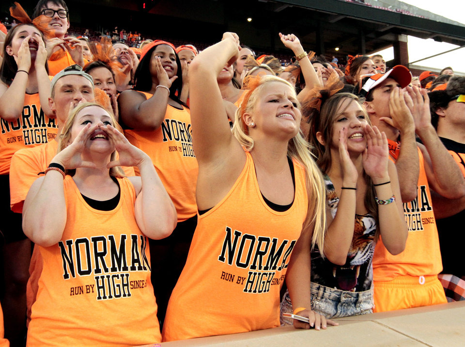 Photo - Norman High School fans Rebekah Abbott, Kaylea Fabri Savannah Piper cheer as their Tigers play Norman North Timberwolves at Gaylord Family-Oklahoma Memorial Stadium in Norman, Okla., on Thursday, Sept. 5, 2013. Photo by Steve Sisney, The Oklahoman