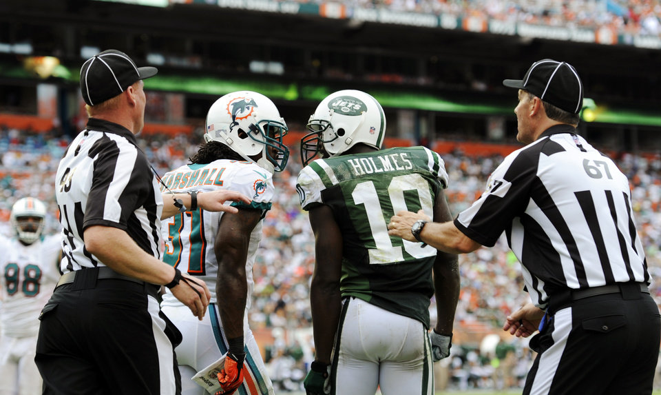 Photo -   Miami Dolphins cornerback Richard Marshall (31) and New York Jets wide receiver Santonio Holmes (10) engage each other as head linesman Greg Maxwell (67) and another official attempt to restrain them during the second half of an NFL football game, Sunday, Sept. 23, 2012, in Miami. (AP Photo/Rhona Wise)