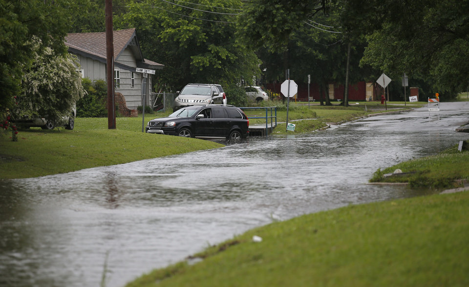 Photo -  High water is pictured near NW 34th and Hammond in Warr Acres, Okla., after severe storms moved through the metro area, Saturday, May 18, 2019. [Sarah Phipps/The Oklahoman]